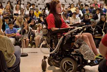Young woman in wheelchair speaks to audience