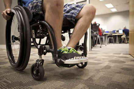Floor-level perspective of man with sneakers sitting in wheelchair