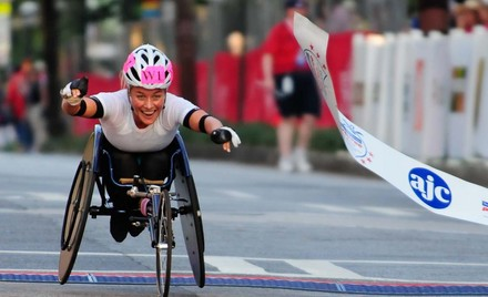 Female hand cyclist crosses finish line of the AJC Peachtree Road Race