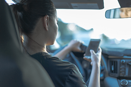 Young woman checks her phone while driving a car