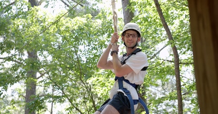 Former brain injury patient hangs from rope swing wearing harness for adaptive wall climbing