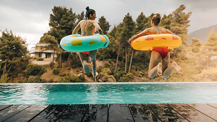 Two girls in inflatable tubes jumping into swimming pool
