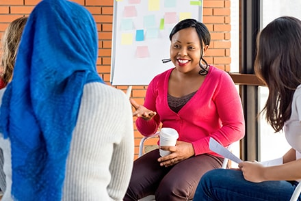 Group of diverse young women talking at a coffee shop