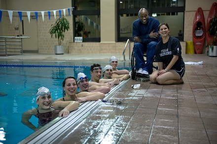 Shepherd Sharks swim team and coaches next to indoor pool