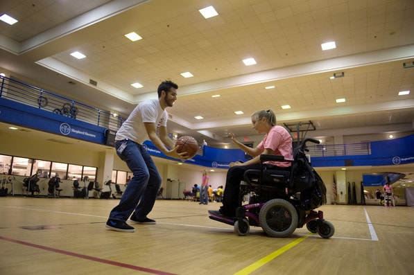 A Shepherd Center patient and staff member play basketball in a gym