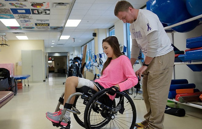 Physician assists adolescent SCI patient in wheelchair