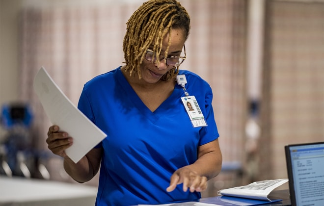 Nurse in blue scrubs reviews paperwork