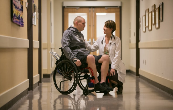 Physician speaks with an SCI rehabilitation patient in a hallway