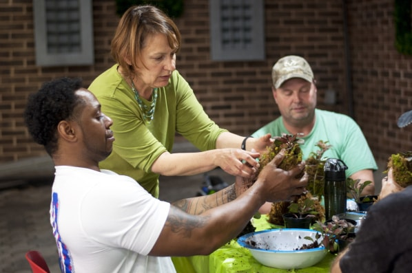 Instructor assists two SHARE military clients with plant care at Shepherd Center's greenhouse