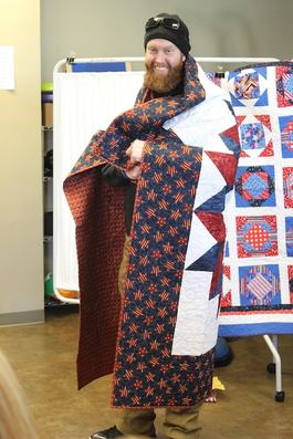 SHARE client receives a blanket from Quilts of Valor to honor military service