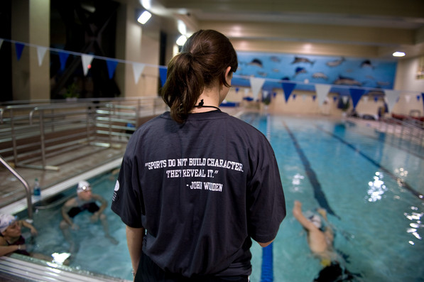 """A person by a pool with the phrase, """"Sports do not build character. They reveal it"""" on her shirt"""