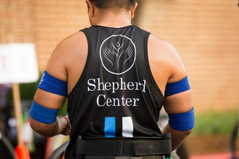 Shepherd Center rehabilitation patient wears athletic shirt and kinesio tape
