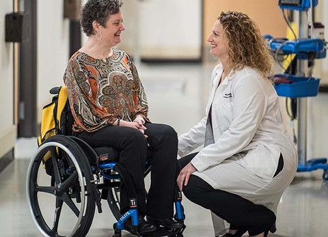 Patient using a wheelchair talks to doctor about patient recovery at Shepherd Center