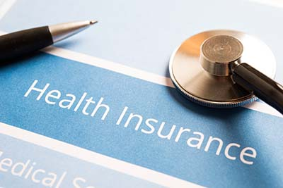 "A stethoscope, pen and the words ""health insurance"""