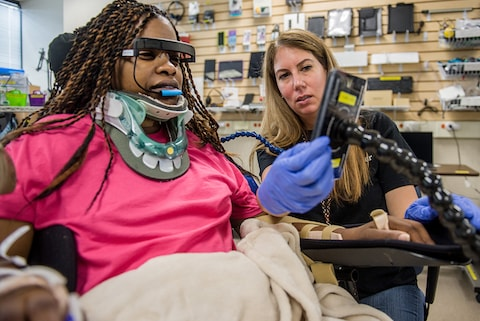 Spinal cord injury patient learning to use assistive technology equipment