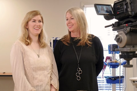 Two smiling women stand in front of video cameras