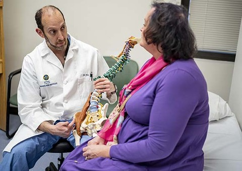 Dr. Eric Shaw at Shepherd Spine and Pain Institute talks with a spinal cord injury patient